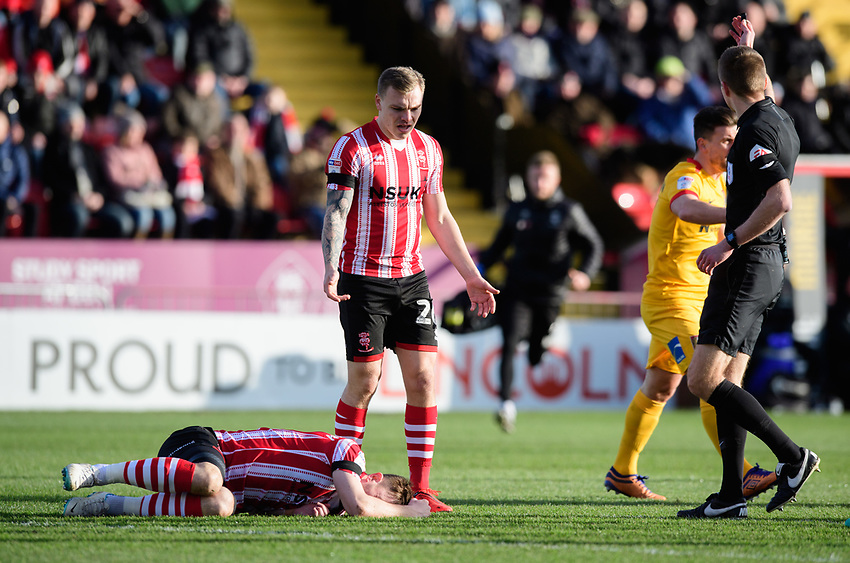Referee Michael Salisbury calls for Lincoln City's head of sports science and medicine Mike Hine to come onto the pitch to treat Lincoln City's Lee Frecklington for an injury<br /> <br /> Photographer Chris Vaughan/CameraSport<br /> <br /> The EFL Sky Bet League Two - Lincoln City v Northampton Town - Saturday 9th February 2019 - Sincil Bank - Lincoln<br /> <br /> World Copyright © 2019 CameraSport. All rights reserved. 43 Linden Ave. Countesthorpe. Leicester. England. LE8 5PG - Tel: +44 (0) 116 277 4147 - admin@camerasport.com - www.camerasport.com