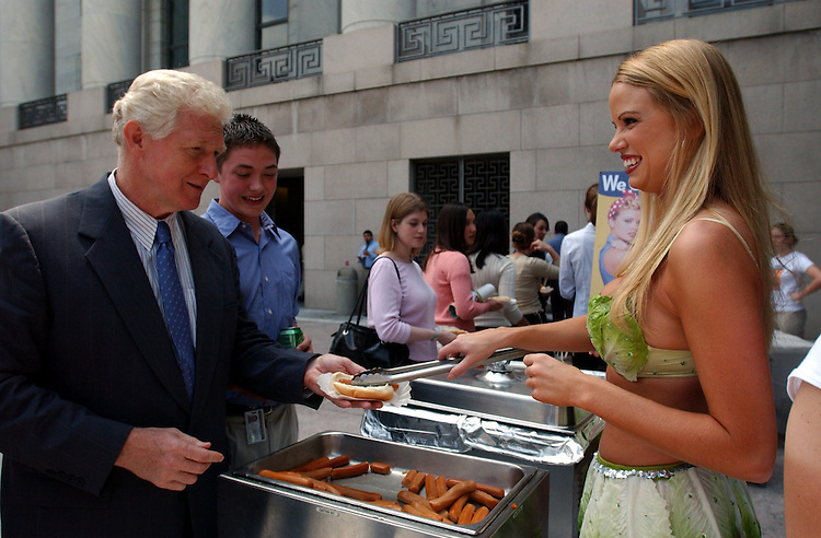 PETA5_072303 -- Wearing a skimpy bikini made of lettuce leaves, Playboy magazine's Miss July 2002, Lauren Anderson serves up a veggie-dog to Jim Moran, D-VA, in front of the Rayburn House Office building.