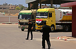 Palestinian security forces stand guards as Egyptian trucks carrying fuel arrive to Gaza's power plant in Nusseirat, in the central Gaza Strip after entering the southern Gaza Strip from Egypt through the Rafah border crossing on June 21, 2017. Egypt began to deliver a million litres of fuel to Gaza, a Palestinian official said, in an attempt to ease the Palestinian enclave's desperate electricity crisis. The fuel, trucked in through the Rafah border between Egypt and Gaza, will be routed to the territory's only power station -- closed since April due to fuel shortages. Photo by Ashraf Amra
