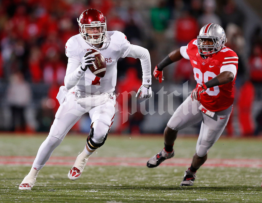 Indiana Hoosiers quarterback Nate Sudfeld (7) is pursued by Ohio State Buckeyes defensive lineman Steve Miller (88) during Saturday's NCAA Division I football game at Ohio Stadium in Columbus on November 23, 2013. Ohio State won the game 42-14. (Barbara J. Perenic/The Columbus Dispatch)