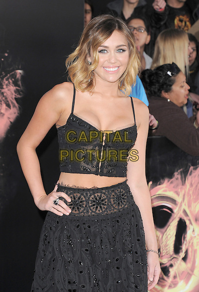 "Miley Cyrus.The World Premiere of ""The Hunger Games"" held at The Nokia Theater Live in Los Angeles, California, USA..March 12th, 2012.half length black lace sheer skirt top belly stomach midriff cleavage hand on hip.CAP/RKE/DVS.©DVS/RockinExposures/Capital Pictures."