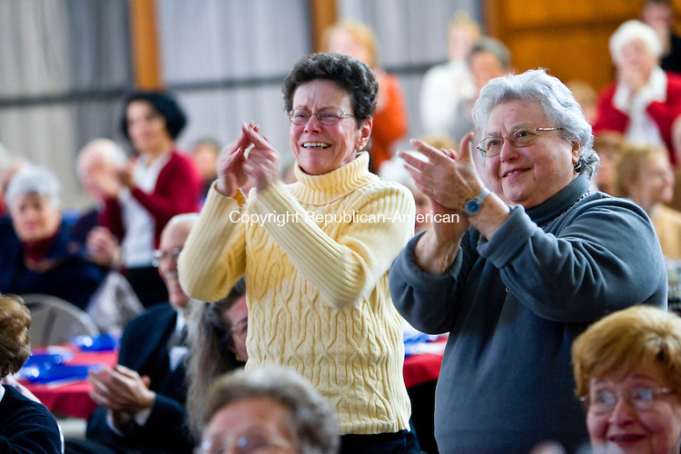 SOUTHBURY, CT - 20 JANUARY 2009 -012009JT01-<br /> Lorraine Marcantonio, left, of Southbury, and Frieda Denenmark, of Heritage Village, stand and applaud after U. S. Pres. Barack Obama took the oath of office as they watched the inauguration projected on a large screen at the Jewish Federation of Western Connecticut in Southbury on Tuesday, during a panel discussion and luncheon.<br /> Josalee Thrift / Republican-American