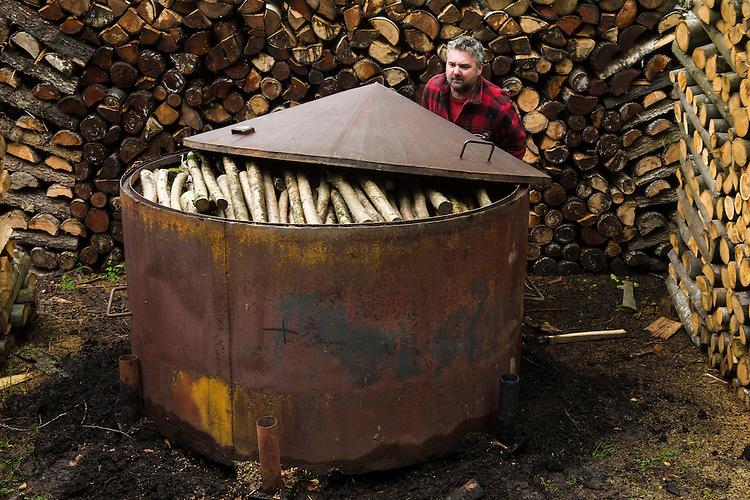 Charcoal production using a traditional charcoal kiln, part of woodland maintenance and restoration at Wakehurst Place - Royal Botanic Gardens, Kew. Ardingly, West Sussex, UK.