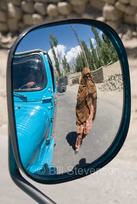 A Pakistani woman reflected in the mirror of a jeep in the town of Skardu Pakistan