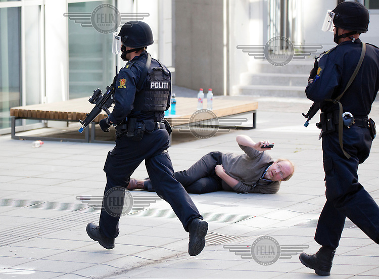 Armed police arrives as a &quot;victim&quot; lies on the ground. Norwegian emergency services practice various scenarios related to violent attacks in a government building in the centre of Oslo.  <br /> <br /> The two terror attacks in Norway July 22 , 2011, left 77 people dead and sparked a debate about the failiures of the police. Since then the autorities have been working to improve the readiness, but exercises prove progress is slow. <br /> <br /> <br /> &copy;Fredrik Naumann/Felix Features