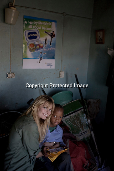 SOWETO, SOUTH AFRICA - SEPTEMBER 1: Mischa Barton, the actress and visit a boy in his home on September 1, 2008 in Soweto, outside Johannesburg, South Africa. Mischa Barton spent 2 days visiting Save The Children supported projects in South Africa, meeting school children and young children. Save The Children are helping about 51,000 children made by HIV/AIDS and poverty to access food, healthcare, social security and education. (Photo by Per-Anders Pettersson/Getty Images For Save The Children)..