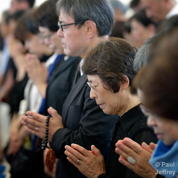 People pray during a moment of silence in a memorial ceremony in Nagasaki, Japan, on August 9, 2015, the 70th anniversary of the day the United States dropped an atomic bomb on the city.