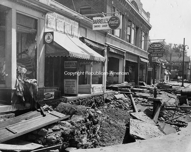 South Main Street Naugatuck looking south from the Maple Street intersection. Notice the force of the Naugatuck River as seen by the depth of the excavations in front of the business establishments.