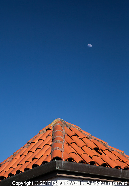 A waxing gibbous moon passes over a tiled roof in downtown San Leandro, California.