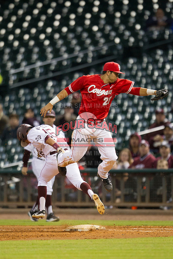 Houston Cougar first baseman Justin Montemayor #20 leaps to catch a high throw as Texas A&M Aggie baserunner Mikey Reynolds #16 crosses first base in the NCAA baseball game on March 1st, 2013 at Minute Maid Park in Houston, Texas. Houston defeated Texas A&M 7-6. (Andrew Woolley/Four Seam Images).