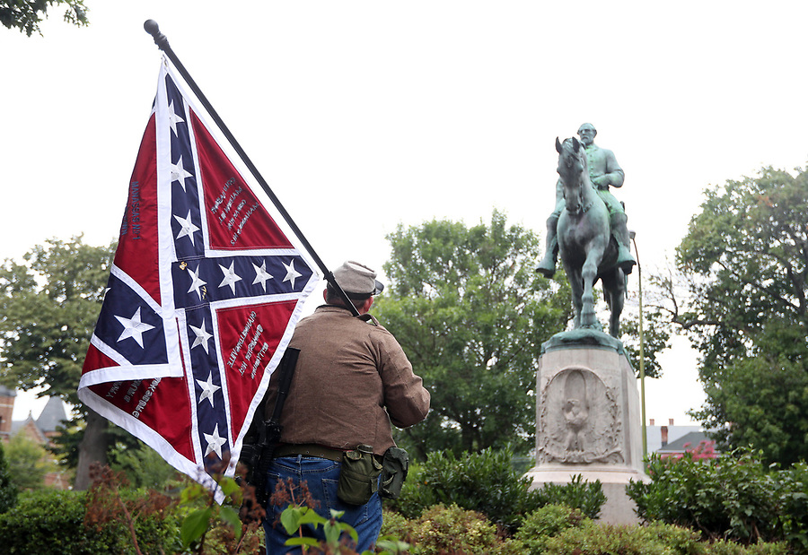 Allen Armentrout of North Carolina wears a Confederate outfit with 2 guns as he stood protecting the Lee Statue Tuesday, Aug. 15, 2017 at Emancipation Park in Charlottesville, Va. A small crowd of Charlottesville residents protested him for 30 minutes before Police escorted Armentrout away from the park.