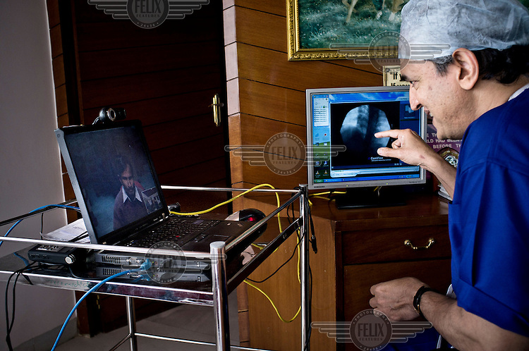 Heart surgeon Dr. Devi Prasad Shetty explains a medical issue  to a patient's father (who is in Calcutta) over the internet during a long distance outpatient's consultation while sitting in his office at the Narayana Hrudayalaya hospital.