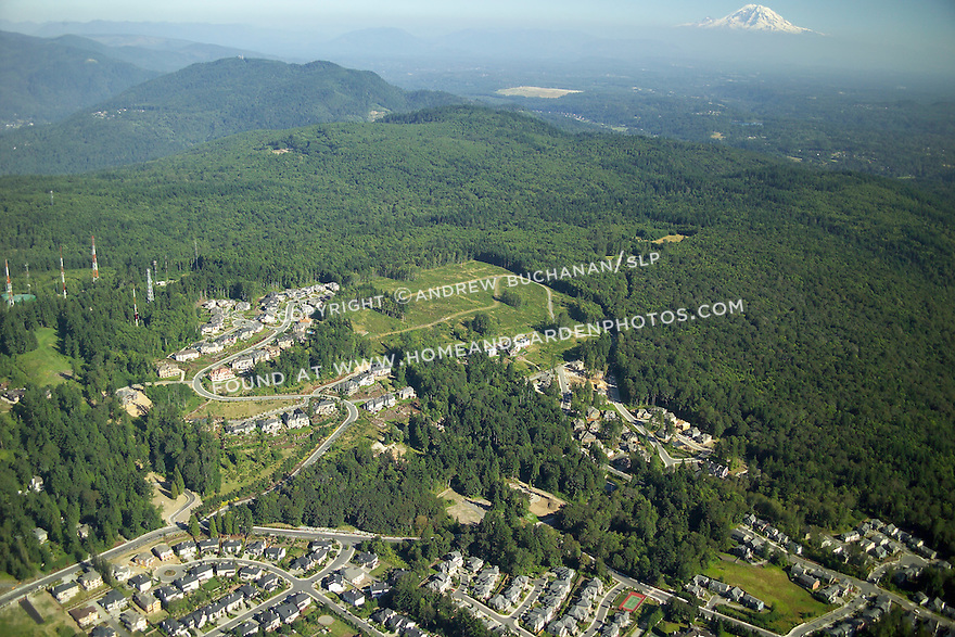 An aerial view of a new suburban development being carved from previously undeveloped land near Cougar Mountain State Park in Bellevue, WA.  The hard edge and solid mass of trees to the right of the development is state park land, while views of Mount Rainer show why these are million dollar lots.