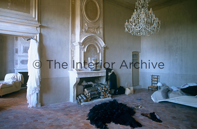 A bedroom in a grand yet minimalist style is furnished with a central chandelier, ornate fireplace and raw plaster walls