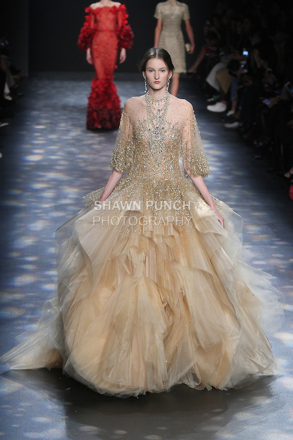 Model Viola walks runway in a gold tulle ball gown with light gold and silver floral embroidery on flutter cape sleeves and sculptural cascading skirt, from the Marchesa Fall 2016 collection by Georgina Chapman and Keren Craig, presented at NYFW: The Shows Fall 2016, during New York Fashion Week Fall 2016.