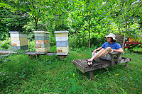A moment for reading, Eve Vaterlaus, artist, painter, sculptor and designer, near the hives at the Green Meadow Waldorf School in Chestnut Ridge. This Steiner school has created a biodynamic garden, which is recognized as an avant-garde program in environmental education.  The future leaders of the green revolution.