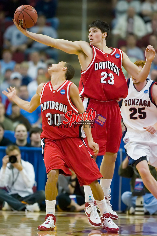 Stephen Rossiter (23) of the Davidson Wildcats grabs a rebound over the head of teammate Stephen Curry (30) late in the second half versus the Gonzaga Bulldogs in the first round of the 2008 NCAA Men's Basketball Championship at the RBC Center in Raleigh, NC, Friday, March 21, 2008.