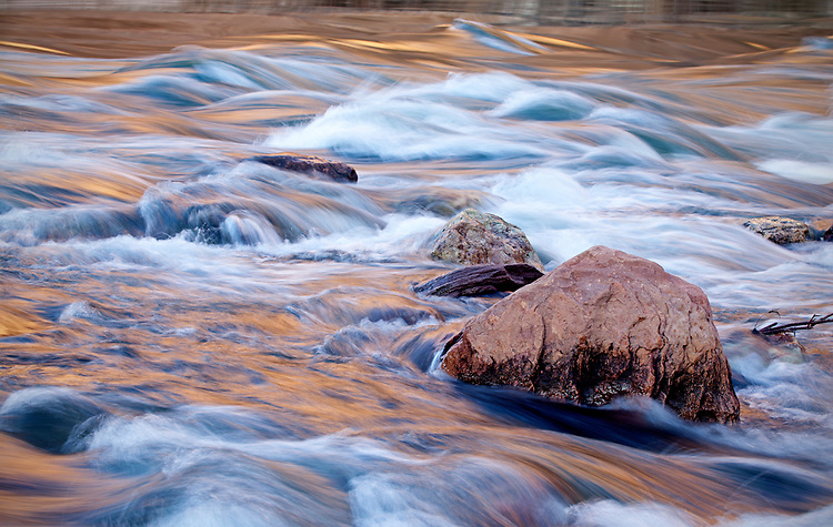 Reflected light from a setting sun makes the Colorado River glow in the Cathedral Rapids in the Grand Canyon National Park, Arizona, USA