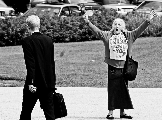 An unidentified woman wearing a Jesus Loves You shirt, waving an American flag walks around the Senate side of the East Front of the Capitol on Oct. 1, 2008.