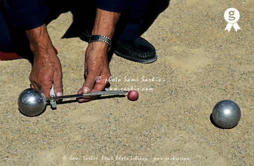 Player of the French boule game measuring distance between two bowls, Provence, France (Licence this image exclusively with Getty: http://www.gettyimages.com/detail/82406741 )