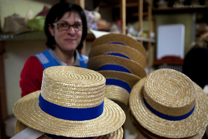 "9 december 2009 - Coustilleres' hat factory, Septfonds, France - Patricia Lopez works since 13 years at the Coustilleres' hat factory. She holds the ""Canotier"" hats as they are ready to sell. .Septfonds is the heart of French straw hat making, due to its very ancient hatter tradition. The hat making industry had its commercial peak in the late 19th century..Coustillères is a family owned hat making factory that has been making straw hats in Septfonds for nearly 100 years. They make hats from straw, felt, and cloth as well as caps. The current owner is Jean-Claude Coustilleres. He is one of the last hat makers of the region..The straw hat making process is very labor intensive and numerous hands are involved. Nearly all of the equipment is over 100 years old, they use the original presses and tools including aluminium molds and sewing machines and dye their own straw continuing the traditional methods of manufacturing. The hat blocking and shaping, straw braids construction and dyeing are all done by hand..The company works on behalf of fashion houses and makes a variety of regional and historical hats. It produces 2 collections a year distributed by a network of salespeople and through a catalog to clients around the world. Photo credit: Benedicte Desrus"