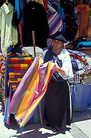 Indigenous woman selling textilesr at the Handicrafts market in Poncho Plaza, Otavalo, Ecuador