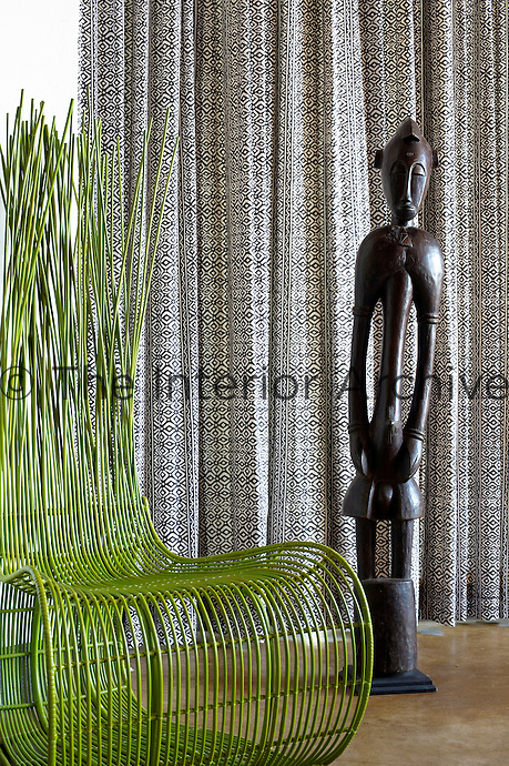 A tribal wood figurine and modern green chair at Singita Pamushana Lodge, Malilongwe Trust, Zimbabwe