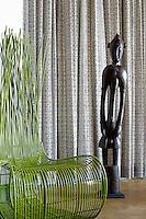A tribal wood figurine and modern green chair at Singita Pamushana Lodge, Malilongwe Trust, Zimbabwe