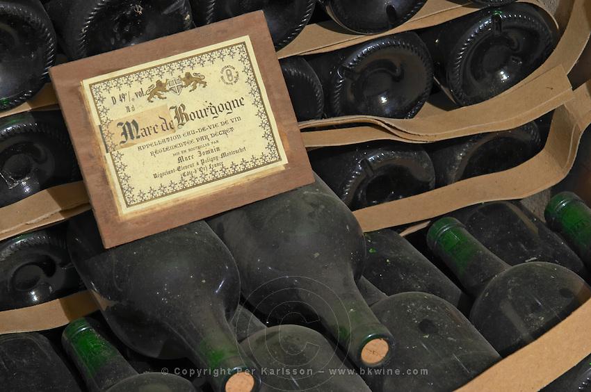 Bottles aging in the cellar. Marc de Bourgogne. Domaine Marc Jomain, Puligny Montrachet, Cote de Beaune, d'Or, Burgundy, France