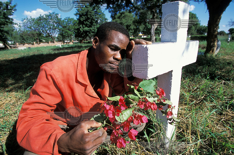 A man grieving at the grave of his wife, who died of AIDS.