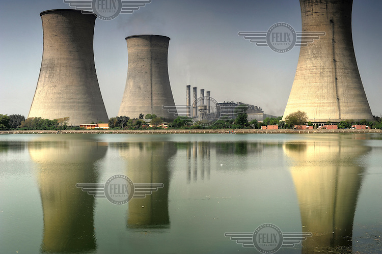 A lake reflects the cooling towers of the Guru Nanak Dev Thermal Power Plant. Some of the output of ash from the coal burnt in the plant escapes into the air and has been speculatively linked to health problems in the area.