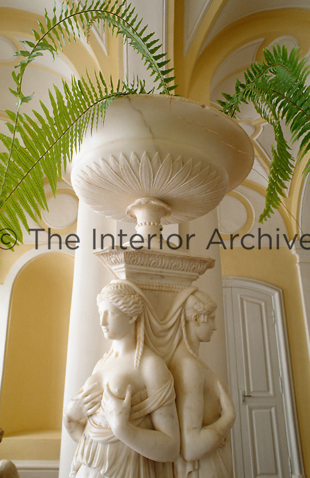A white marble sculpture of a pair of women standing back to back support a large urn