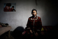 Sun Zhan Xia sits in her bedroom in Qingdun Village, Gangyun County, Jiangsu, China.  She and husband Zhao Xia You care for their two grandchildren Zhao Shi (male, 6) and Zhao Min (female, 9) who were orphaned in 2007.  The children's father, Sun Zhan Xia's son, died of hepatitis in 2006 and their mother was forced to remarry and abandon the children in 2007.  Sun Zhan Xia and her husband are both over 60 and in bad health.  The couple owes approximately 40,000 RMB (about $5,300 USD) to pay for the medical treatment of their dead son, the children's father.  Due to their health situation and this enormous debt, the pair cannot afford to care for the children any longer, and the children are in danger of being placed in orphanages.  ..At the time of the picture, China's Amity Foundation charity, was investigating the family's situation in preparation to raise money to financially support these children and other orphans in similar situations.  With Amity's support, each orphan, aged 6-12, would receive approximately 1,400 RMB annually (about 200 USD) to pay for the cost of living. Amity works to keep children out of the institutional orphanages in China, preferring to provide monetary assistance that can help maintain a family environment for the orphans it helps.