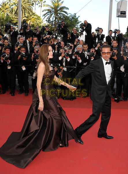 ANGELINA JOLIE & BRAD PITT.'The Tree of Life' premiere at the Palais des Festival, 64th International Cannes Film Festival, France.16th May 2011.full length strapless silk satin brown dress gown black tux tuxedo tinted glasses sunglasses shades couple gathered goatee facial hair hand arm side profile holding hands photographers press.CAP/PL.©Phil Loftus/Capital Pictures.