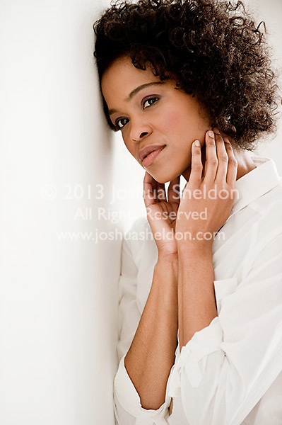 Young African American woman leaning against white wall