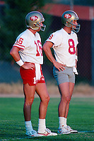 ROCKLIN, CA - Steve Young (right) and Joe Montana of the San Francisco 49ers stand on the sidelines during practice at training camp at Sierra College in Rocklin, California in 1988. Photo by Brad Mangin