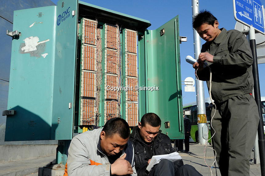 Chinese workers from CNC (China Netcom Group Corporation) check telephone lines in Beijing, China. CNC is a provider of wire-line telecommunications services in mainland China, mainly to areas in the north of China. China Netcom was Beijing 2008 Olympic Official telecommunication operator..