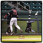 Third baseman Jared Williams (1) of the North Greenville Crusaders flips over the dugout railing in an unsuccessful attempt at a pop foul in the sixth inning of a game against the Queens University Royals on Tuesday, March 12, 2019, at Fluor Field at the West End in Greenville, South Carolina. Williams remained in the game. The catcher is Lex Tuten (23). North Greenville won, 14-3. (Tom Priddy/Four Seam Images)