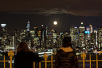 People watch the moon rise along the skyline of Middle Manhattan while it is seen from Weehawken in New Jersey March 27, 2013. Photo by Eduardo Munoz Alvarez / VIEWpress.