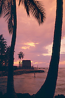 Coconut palms and Hale O Keawe Heiau at sunset<br /> Pu'uhonua O Honaunau National Historical Park<br /> (City of Refuge)<br /> Island of Hawaii,  Hawaii