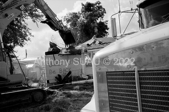 Saint Bernard's Parish, Louisiana.May 26, 2006..Demolition teams work at leveling as many as 6,000+ homes in St. Bernard's Parish damaged by hurricane Katrina in August of 2005...FEMA is offering to destroy home for free up until June 30, 2006. About 12 homes are being demolished a day (so far). ..Workers are outfitted in special clothing and masks and water is poured on to the debris as the homes have asepses. The water is to keep down the asepses fumes...The demolition of a home begins.