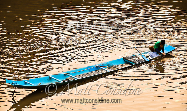The boatman draws in his net on his long boat with his catch of fish.<br /> (Photo by Matt Considine - Images of Asia Collection)