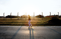 A girl skates along the Birkenau perimeter road headed from the adjacent village of Brzezinka to the town of Os›wie™cim. The road separates farmland and houses circling the death camp museum. A buffer zone of 100 meters was established to limit development near Auschwitz - Birkenau, but some of the land had already been settled by the time the law was enacted.