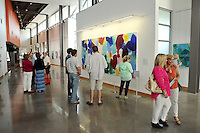 STAFF PHOTO BEN GOFF  @NWABenGoff -- 07/18/14 Visitors peruse paintings in the 'Connecting the Dots' exhibit by artist Heidi Carlsen-Rogers of Bella Vista, during the grand opening of STORY: The Galley at Grace Point at Grace Point Church in Bentonville on Friday July 18, 2014.