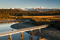 Sunset over Southern Alps with Mt. Tasman and Mt. Cook. Three Mile Lagoon and hiker on bridge, Westland Tai Poutini National Park, West Coast, UNESCO World Heritage Area, New Zealand, NZ