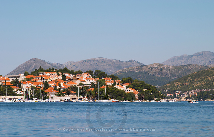 Pleasure boats moored on buoys and along the key, villas along the coast. Mountains mountain tops in the background. Luka Gruz harbour. Babin Kuk peninsula. Dubrovnik, new city. Dalmatian Coast, Croatia, Europe.