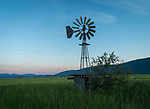 An old wind vane watching over the fields at sunset