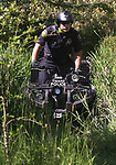 Tigard Police officer Gabe Maldonado patrols an area along the Fanno Creek Trail on a all terrain vehicle where homeless people camp.<br /> Photo by Jaime Valdez
