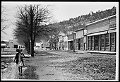 View of Dolores main street, which is still dirt/mud, with businesses lining the street.<br /> RGS  Dolores, CO  Taken by Mollette, Erskine (Rex) - ca. 1912-1914