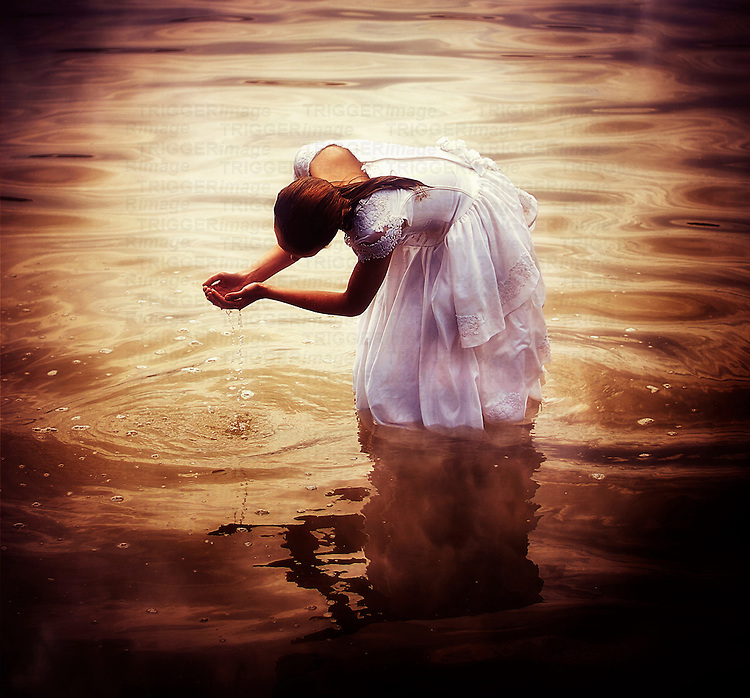 Female youth wearing a white dress standing in a lake with water falling through her fingers